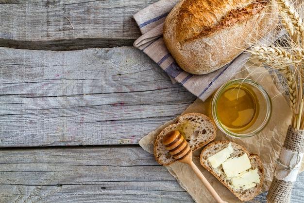 Brot, roggen, weizen, honig, rustikaler hölzerner hintergrund der milch Premium Fotos