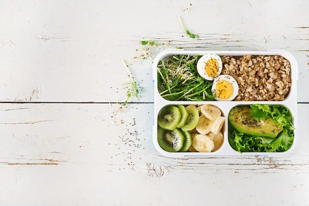 Brotdose mit gekochten eiern, haferflocken, avocado, mikrogrüns und früchten. gesundes fitnessfutter. wegbringen. brotdose. ansicht von oben Premium Fotos