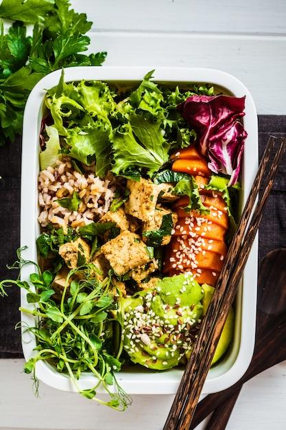 Brotdose mit gesundem veganen essen. bento box mit reis, süßkartoffel, tofu und gemüse. Premium Fotos