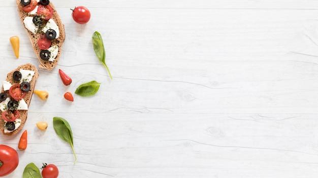 Brotscheiben mit tomatenspitze; käse und oliven über weißen tisch Kostenlose Fotos