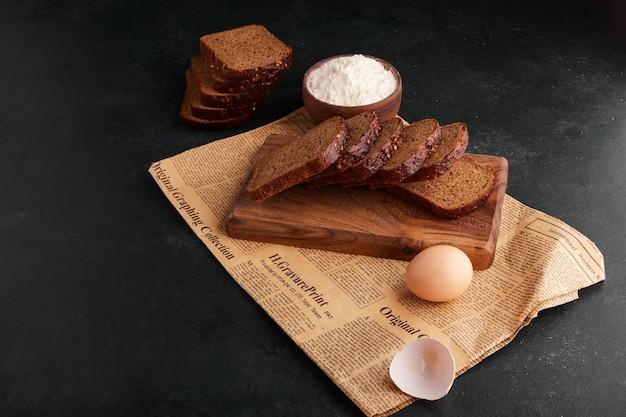 Brotscheiben mit zutaten auf dem stück zeitung. Kostenlose Fotos