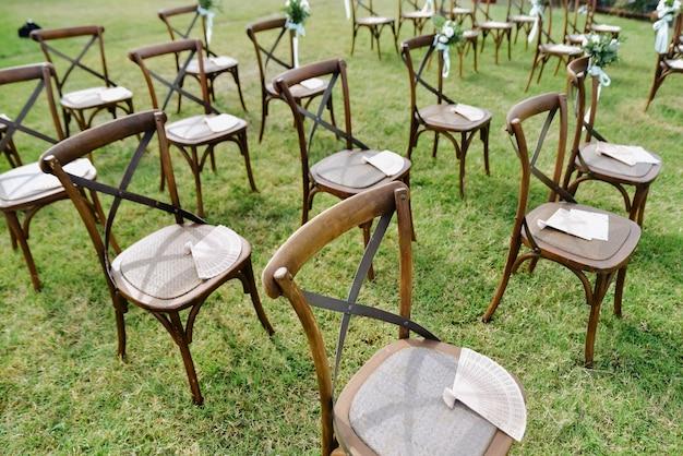 Brown chiavari stühle und handfächer im freien auf dem rasen Kostenlose Fotos