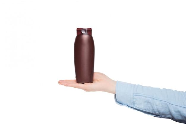 Brown-flasche für kosmetik in einer weiblichen hand, modell, isolat Premium Fotos