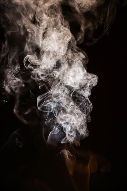 Brown-gewellter rauch auf schwarzem hintergrund Kostenlose Fotos