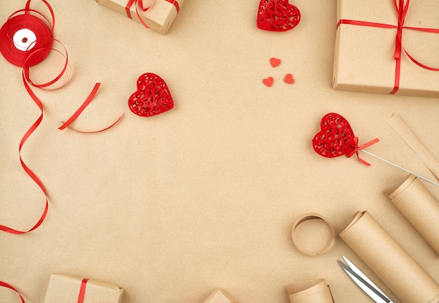 Brown-kraftpapier, verpackte geschenkbeutel und gebunden mit einem roten band, roter herzhintergrund Premium Fotos
