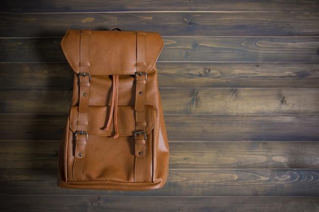 Brown-ledertasche auf holztisch. ansicht von oben. reise-konzept. Premium Fotos