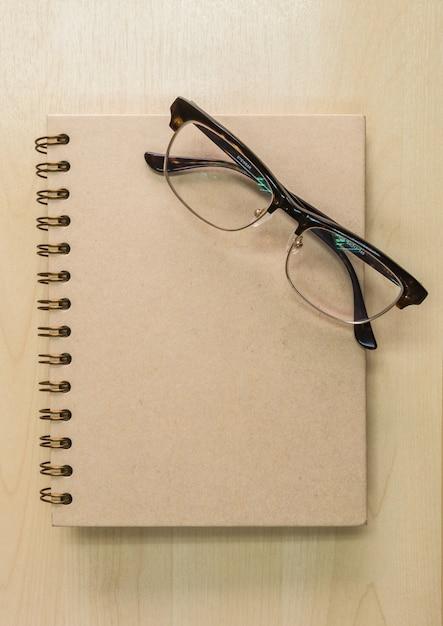 Brown-notizbuch mit brillen auf hölzernem hintergrund Premium Fotos