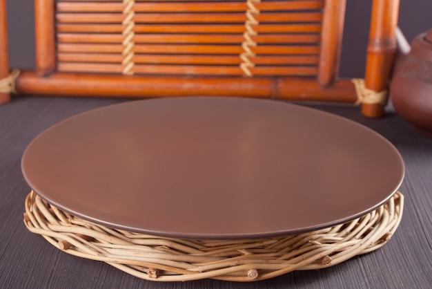 Brown-platte auf der hölzernen alten tabelle. sitzordnung bei tisch. orientalisches thema. Premium Fotos