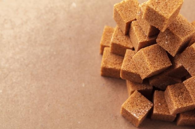 Brown-rohrzuckerwürfel auf einem hellbraunen hintergrund Premium Fotos