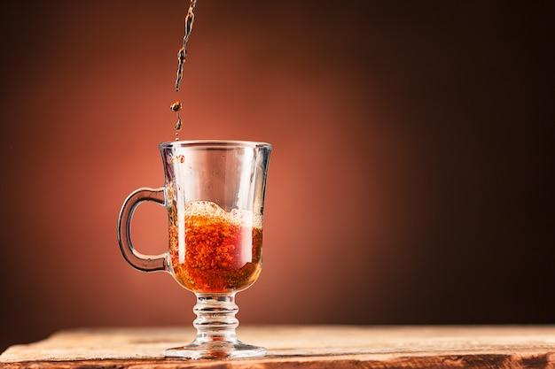 Brown spritzt getränk von der tasse tee auf einer braunen wand heraus Kostenlose Fotos