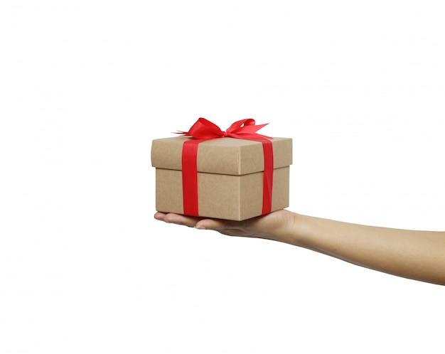 Brown-weihnachtsgeschenkbox auf der hand einer frau lokalisiert auf weißem hintergrund. Premium Fotos