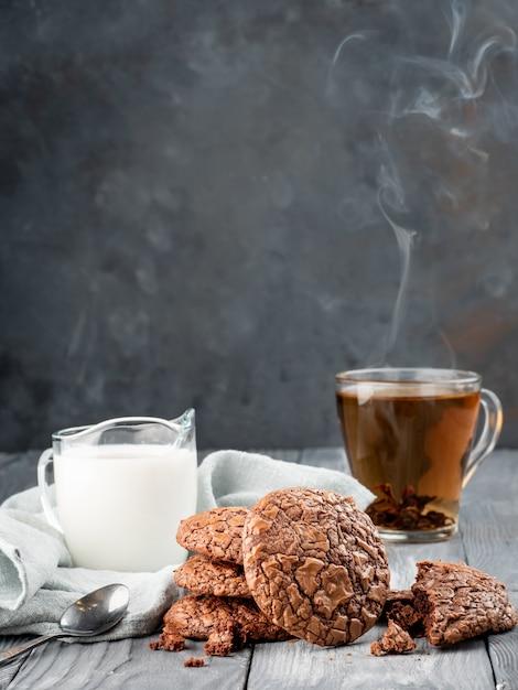 Brownie kekse auf einem holztisch mit tee und milch. kopieren sie platz. Premium Fotos
