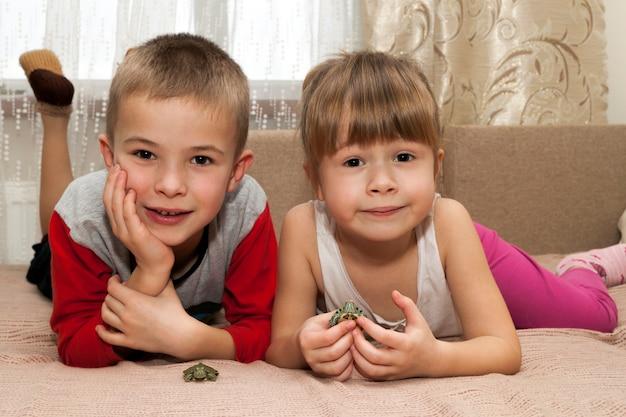 Bruder und schwester des kleinen jungen und des mädchens, die zusammen mit kleinen schildkrötentierhaustieren spielen Premium Fotos