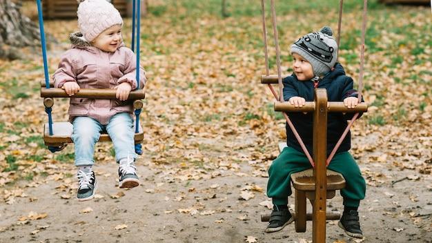 Bruder und schwester, die im park schwingen Kostenlose Fotos