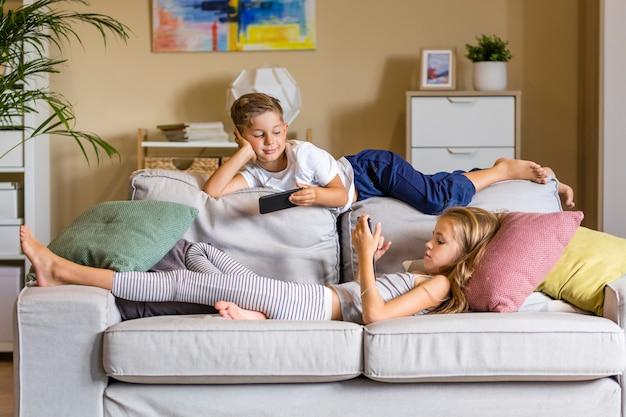 Bruder und schwester im wohnzimmer sitzen auf der couch Kostenlose Fotos
