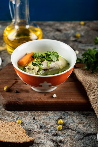 Brühe suppe mit kräutern, kartoffeln und karotten in einer roten schüssel Kostenlose Fotos