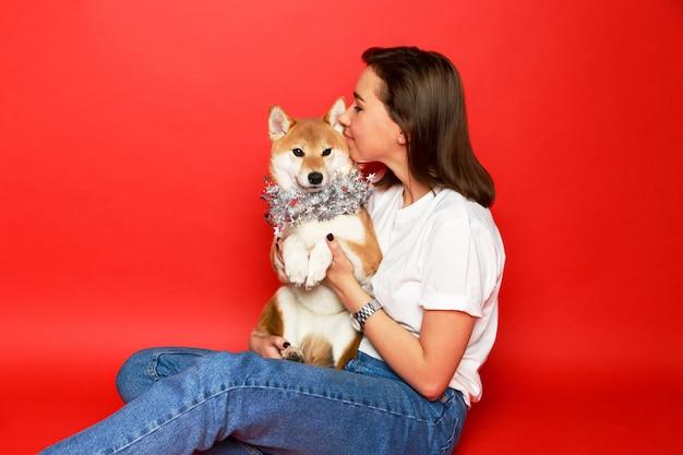 Brünette frau, die shiba inu hund in weihnachtsdekorationen, roten hintergrund umarmend umarmt. liebe zu den tieren Premium Fotos