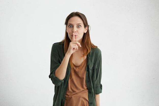 Brünette frau mit glattem haar trägt grüne jacke, hält ihren zeigefinger auf den lippen und macht ein stilles zeichen, das darum bittet, nicht laut zu sein. Kostenlose Fotos