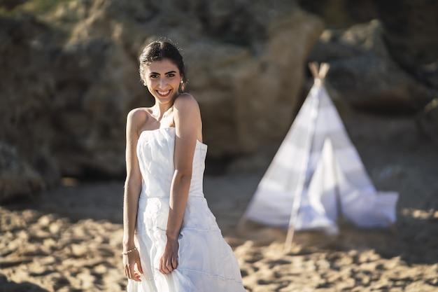 Brünette kaukasische braut, die lächelt, während sie am strand aufwirft Kostenlose Fotos