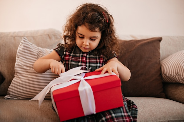 Brünettes kind, das geburtstagsgeschenk öffnet. innenaufnahme des jugendlichen mädchens mit geschenk. Kostenlose Fotos