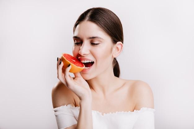 Brünettes mädchen mit gesunder haut beißt saftige rote grapefruit. nahaufnahmeporträt der frau in großer stimmung auf isolierter wand. Kostenlose Fotos