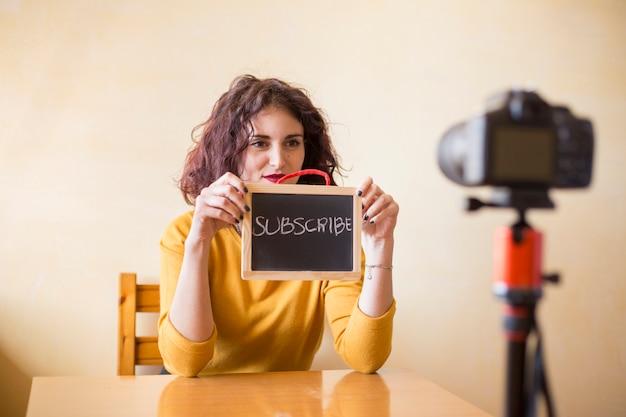 Brunette blogger, der tafel zur kamera zeigt Kostenlose Fotos