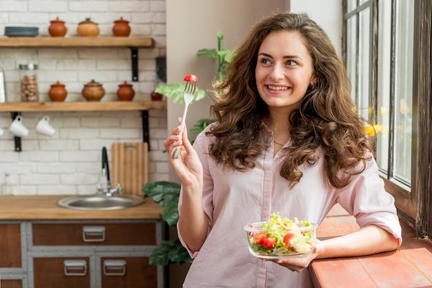 Brunettefrau, die einen salat isst Kostenlose Fotos