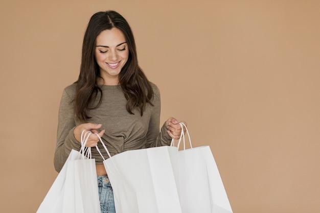 Brunettefrau, die in den einkaufstaschen schaut Kostenlose Fotos