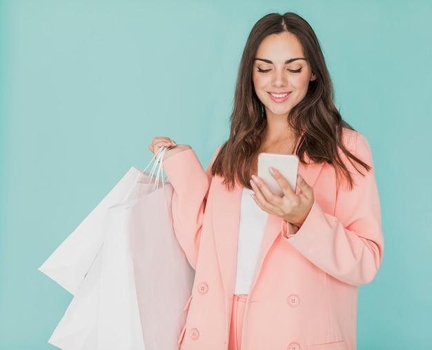 Brunettefrau in der rosa jacke, die smartphone betrachtet Kostenlose Fotos