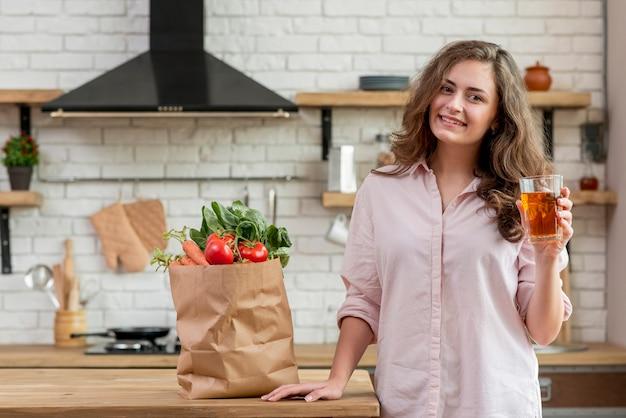Brunettefrau mit einer papiertüte voll vom gesunden lebensmittel Kostenlose Fotos