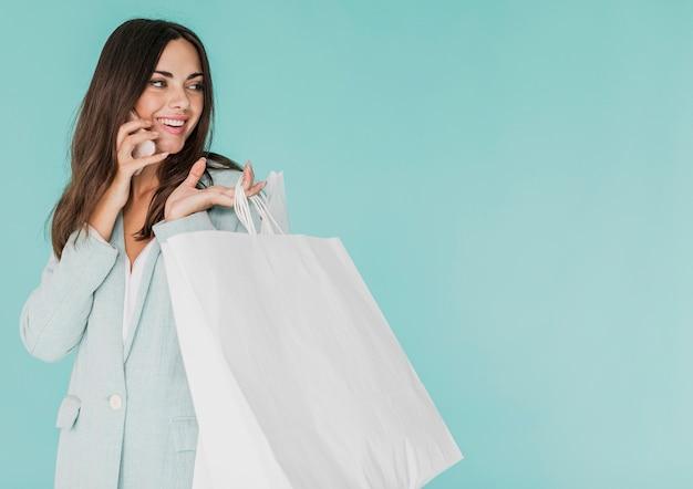 Brunettefrau mit einkaufstaschen sprechend am telefon Kostenlose Fotos