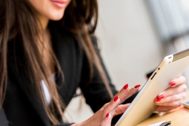 Brunettegeschäftsfrau, die ihre tablette verwendet Kostenlose Fotos