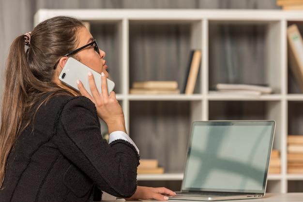Brunettegeschäftsfrau, die in ihrem büro spricht Kostenlose Fotos