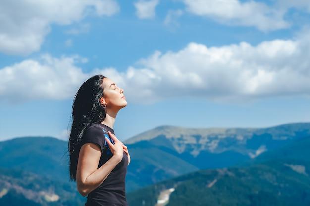 Brunettemädchen auf die oberseite des berges frischluft genießend Premium Fotos