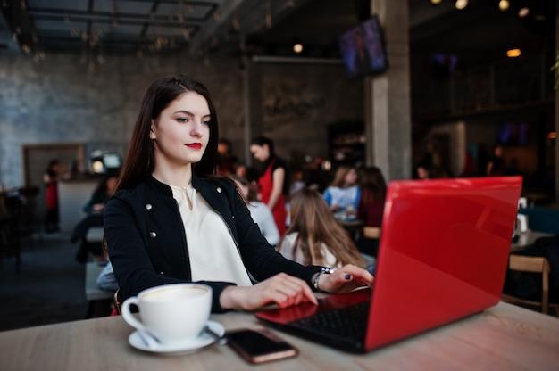 Brunettemädchen, das auf café mit schale cappuccino, arbeitend mit rotem laptop sitzt. Premium Fotos