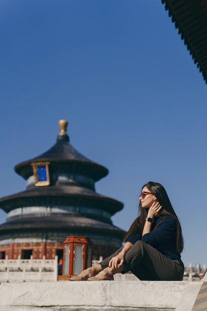 Brunettemädchen, das auf den schritten durch tempel von heven in china sitzt Kostenlose Fotos
