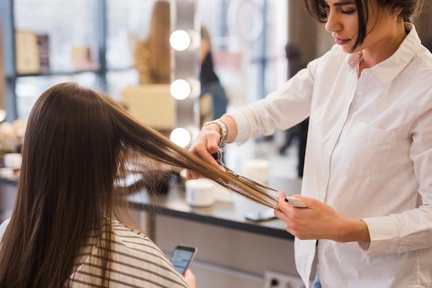 Brunettemädchen, das ihren haarschnitt erhält Kostenlose Fotos