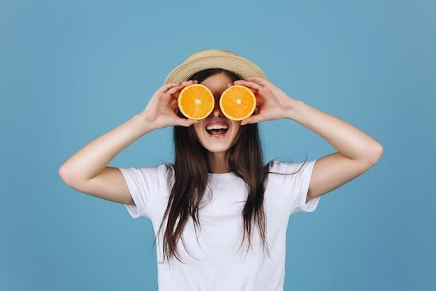 Brunettemädchen im gelben rock hält orangen vor ihren augen und lächelt Kostenlose Fotos