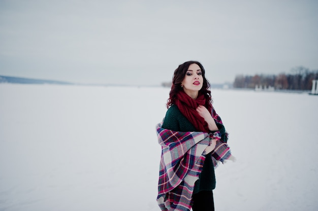 Brunettemädchen in der grünen strickjacke und im roten schal mit gefrorenem see des plaids im freien am abendwintertag. Premium Fotos