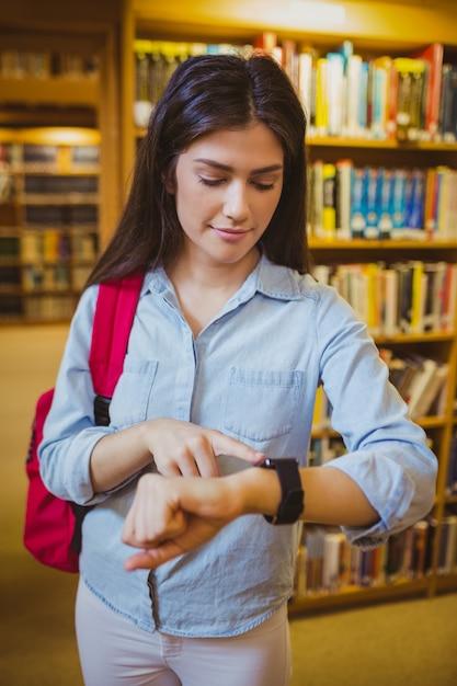 Brunettestudent, der ihre intelligente uhr in der bibliothek verwendet Premium Fotos