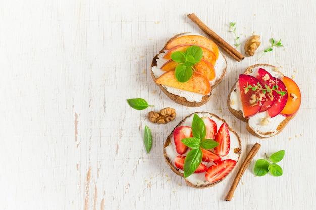 Bruschetta mit pfirsichen, pflaumen, erdbeeren und quark. Premium Fotos
