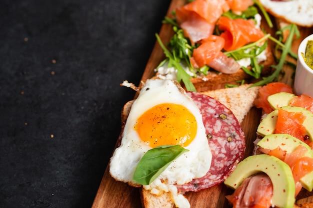 Brushetta oder sandwich auf dem brett über schwarzem beton gesetzt Premium Fotos