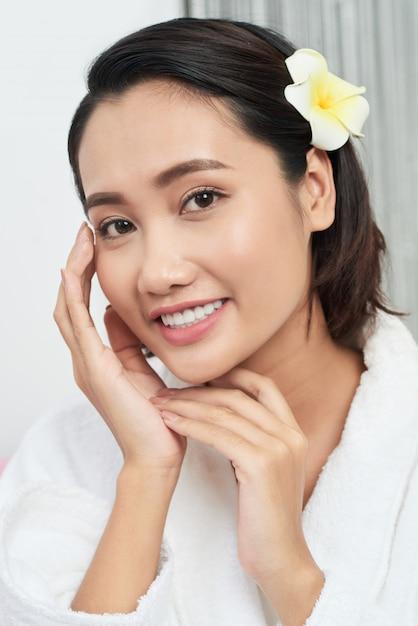 Brustaufnahme eines schönen asiatischen mädchens, das ihr perfektes gesicht mit einer blume in ihrem haar berührt Kostenlose Fotos