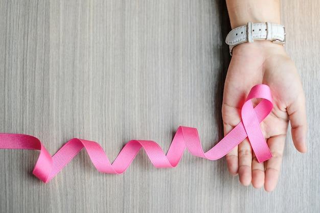 Brustkrebs-bewusstsein, frauenhand, die rosa band hält Premium Fotos