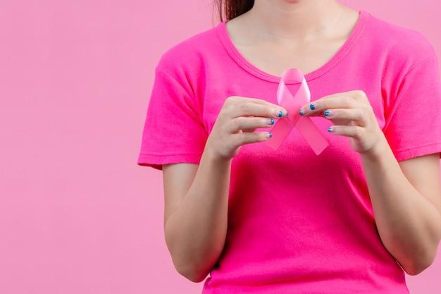Brustkrebs-bewusstsein montn, frauen, die rosa hemden tragen ein rosa band mit beiden händen halten zeigen sie den symbolthe tag gegen brustkrebs Kostenlose Fotos