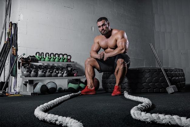 Brutal starke sportliche männer bodybuilder trainiert im fitnessstudio Premium Fotos