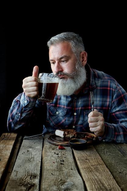 Brutaler grauhaariger erwachsener mann, verrückt nach senfsteak und bier Premium Fotos