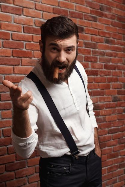Brutaler junger hübscher mann, der zigarre auf ziegelmauer raucht. Kostenlose Fotos