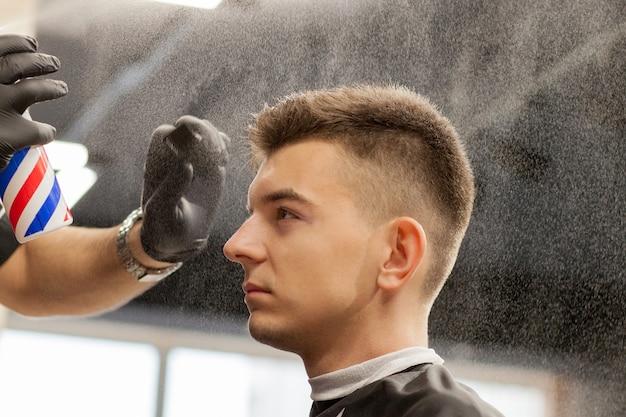 Brutaler kerl im modernen friseursalon. friseur macht frisur einen mann. meister friseur macht frisur mit haarschneidemaschine. konzept friseursalon Premium Fotos