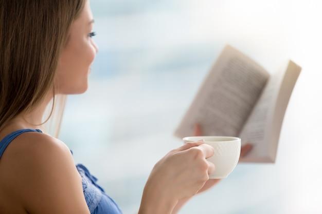 Buch der jungen frau lese, tasse kaffee anhalten Kostenlose Fotos